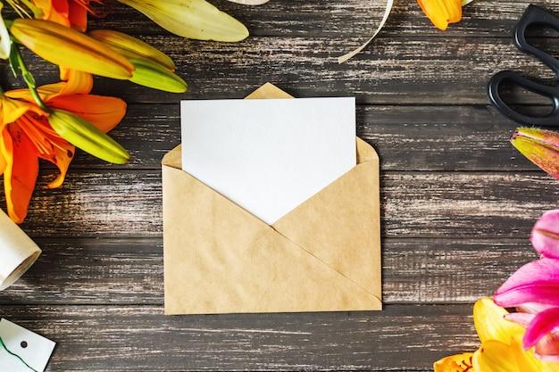Folha vazia branca no envelope do ofício e decorações com as flores na tabela de madeira. layout para o cartão. mock up vista superior