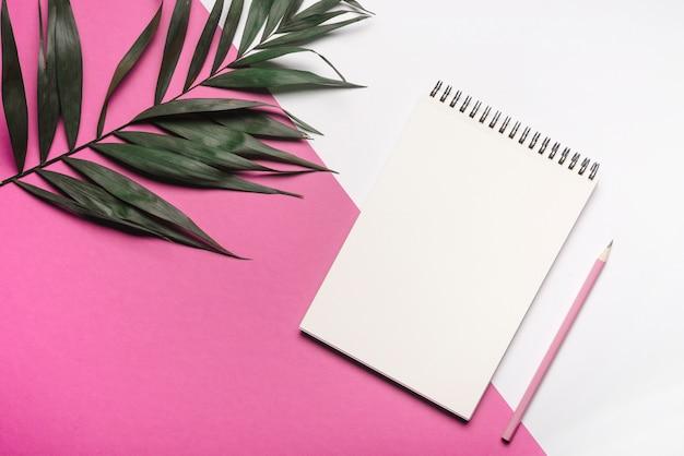 Folha verde com o bloco de notas e o lápis espirais em branco no fundo duplo