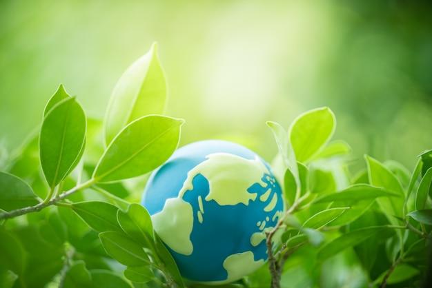 Folha verde com o globo do mundo com espaço da cópia usando-se como o conceito feliz do dia da terra.