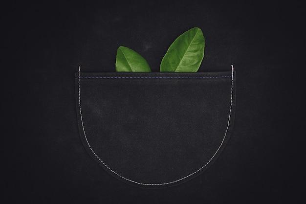 Folha verde e bolsa de couro com padrão de ponto de linha. representando um trabalho natural em defesa de um ambiente verde