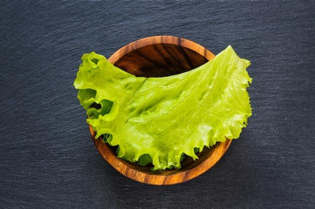 Folha verde fresca da alface na bacia de madeira na pedra preta da ardósia como o fundo do alimento. vista plana superior