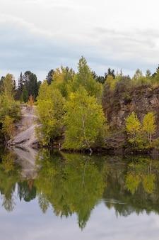 Folhagem de outono refletida em um lago com uma superfície de água espelhada em vidro.