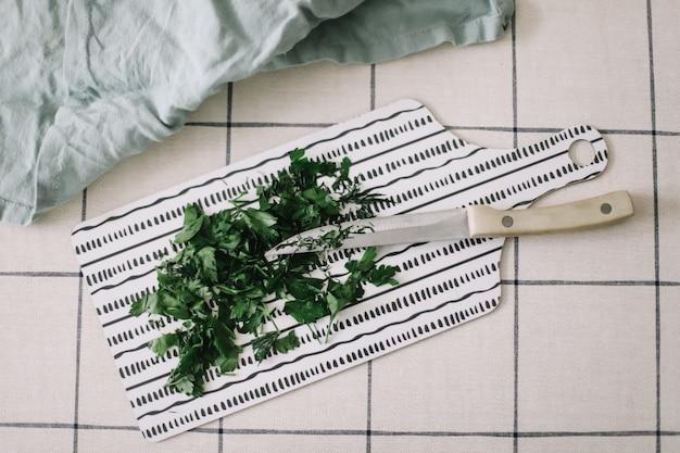 Folhagem de salsa fresca com faca e toalha de cozinha na vista superior da tábua