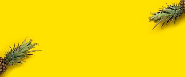 Folhagem verde de abacaxi em um fundo amarelo. vista superior, configuração plana. bandeira.