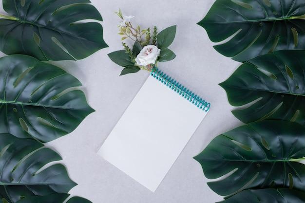 Folhas artificiais, caderno e flor branca na superfície branca.