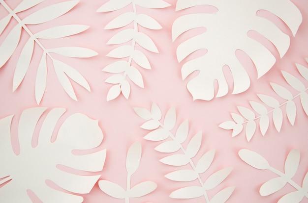 Folhas artificiais estilo de corte de papel com fundo rosa