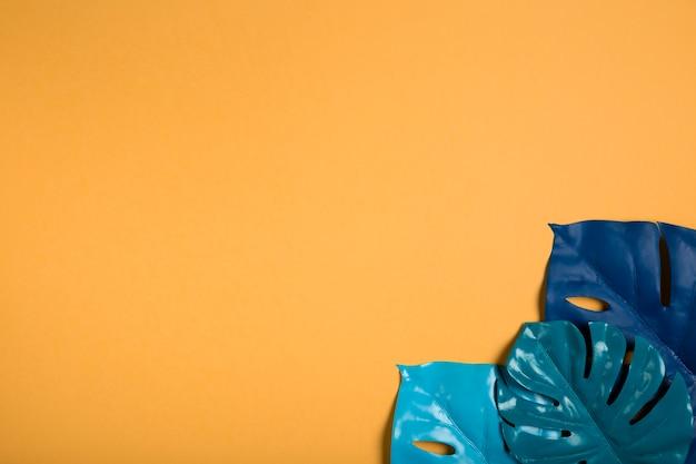 Folhas azuis no papel de parede laranja com espaço de cópia