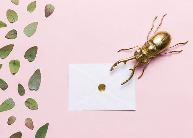 Folhas, besouro e envelope