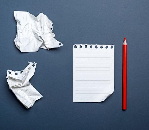 Folhas brancas em branco em uma linha de um bloco de notas e lápis de madeira vermelho