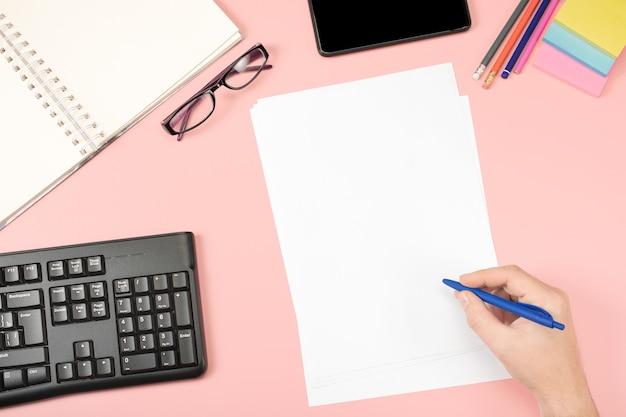 Folhas brancas limpas para registros, mão segura caneta, óculos de escritório. postura plana. conteúdo do office. mesa rosa