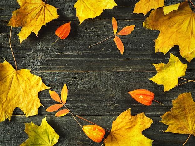 Folhas brilhantes de outono em uma mesa de madeira