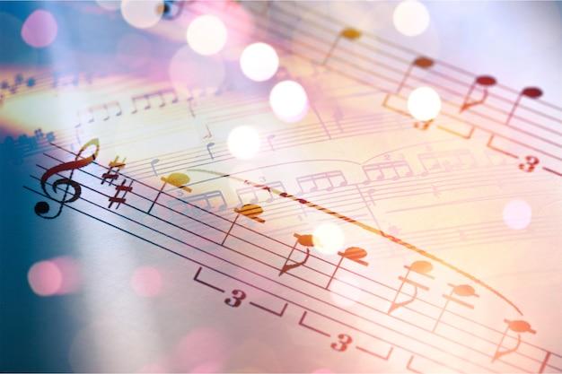 Folhas com notas musicais e bokeh claro abstrato