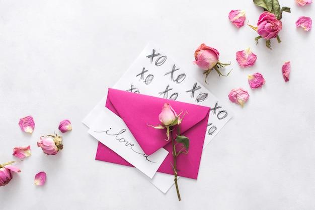 Folhas com títulos, envelope, pétalas e flores
