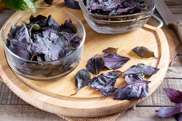 Folhas congeladas de manjericão com manjericão fresco em uma mesa de madeira. vegetais congelados. conceito de alimentação saudável.
