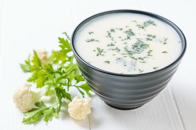 Folhas da salsa, inflorescências da couve-flor e uma bacia da sopa de creme na tabela branca.