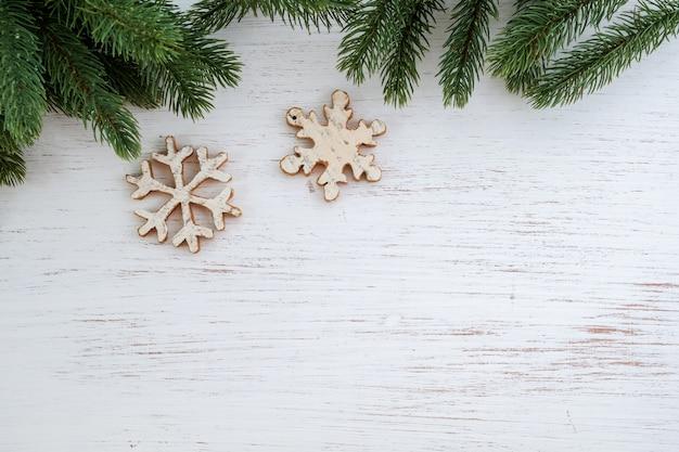 Folhas de abeto de fundo de natal e elementos rústicos, decorando na mesa de madeira branca. layout criativo e composição da vista superior com design de espaço de borda e cópia.