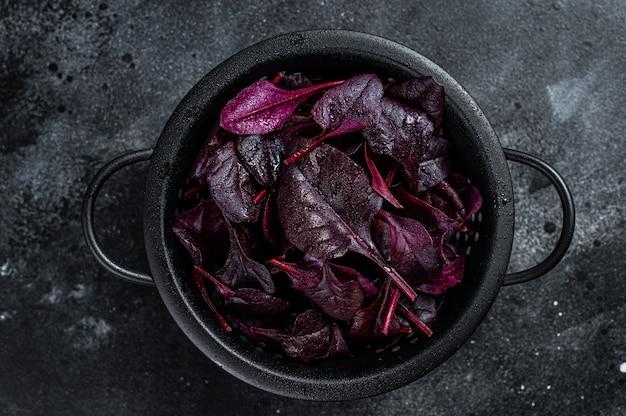 Folhas de acelga vermelha suíça ou salada mangold em uma peneira.