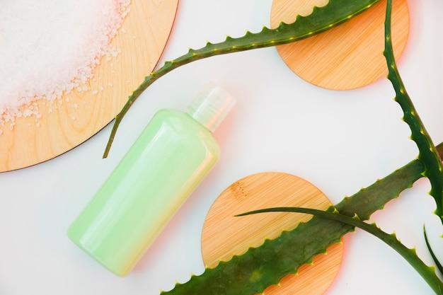 Folhas de aloe vera com um frasco de creme de beleza