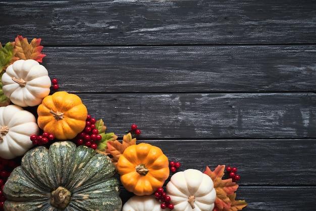 Folhas de bordo do outono com bagas da abóbora e do vermelho no fundo de madeira. projeto de ação de graças