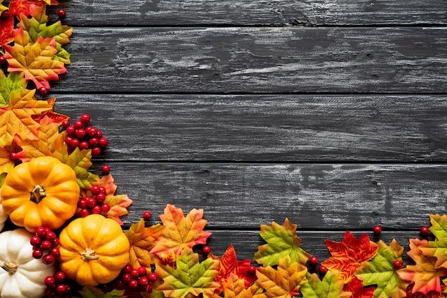 Folhas de bordo do outono com bagas da abóbora e do vermelho no fundo de madeira velho.