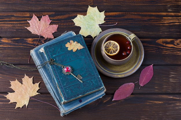 Folhas de bordo, livros antigos e chá em um copo com limão