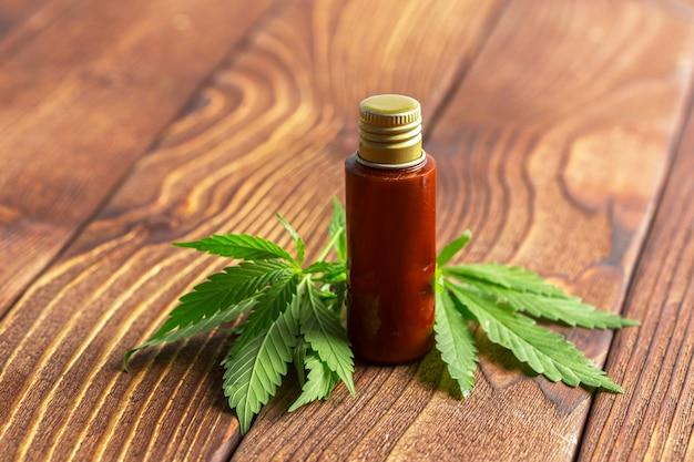 Folhas de cannabis e óleo no fundo de madeira