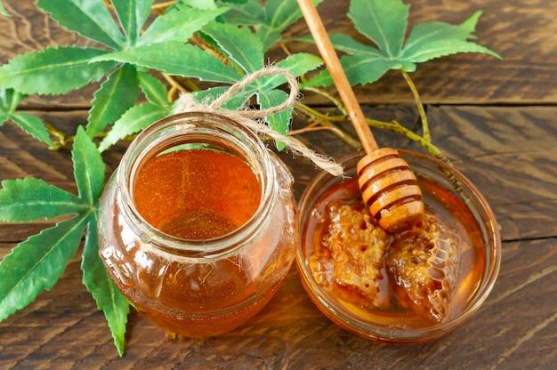 Folhas de cannabis, maconha e mel puro orgânico fresco em frasco de vidro no fundo da mesa de madeira. conceito de mel cbd.