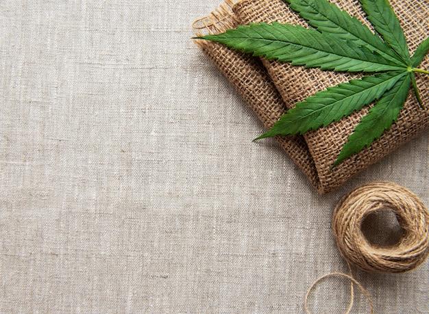Folhas de cannabis no fundo de tecido de cânhamo grosso