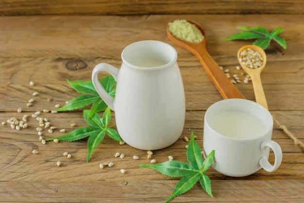 Folhas de cannabis sem glúten vegan e leite sem lactose e cannabis na mesa de madeira.