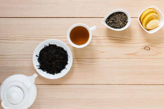 Folhas de chá com chaleira e rodelas de limão