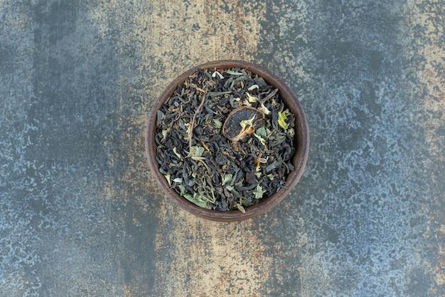 Folhas de chá de ervas em uma tigela de madeira.
