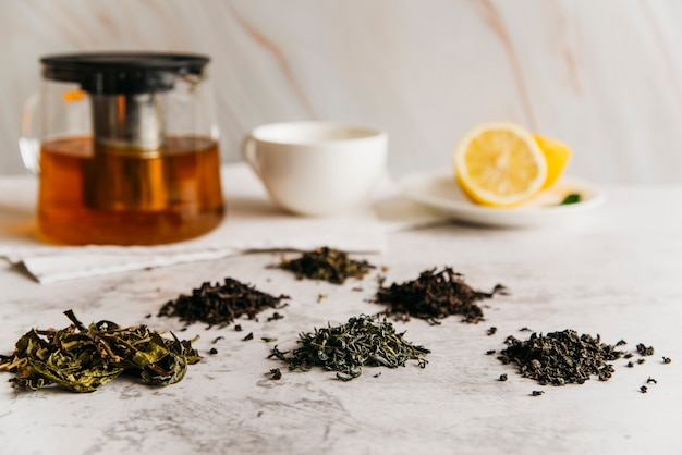 Folhas de chá de ervas secas com chá e limão no pano de fundo texturizado em mármore