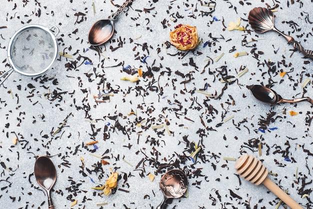 Folhas de chá para a fabricação de cerveja e colheres em um fundo cinzento. copie o espaço.