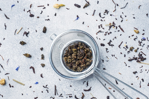 Folhas de chá para a fabricação de cerveja em um filtro em um fundo cinzento. copie o espaço.