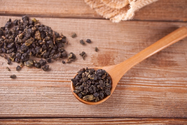 Folhas de chá preto seco com colher de pau na mesa de madeira