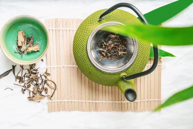 Folhas de chá secas chinesas com bule decorado com folhas de bambu. conceito de relaxamento. Foto Premium