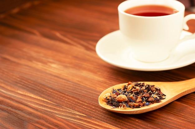 Folhas de chá secas em uma colher de pau e chá fervido em uma caneca branca na mesa