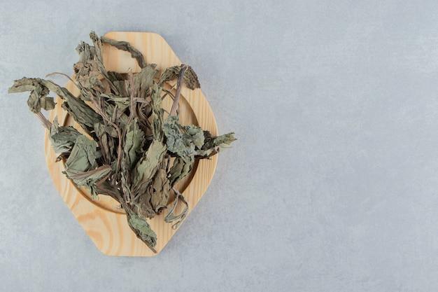 Folhas de chá secas na placa de madeira.