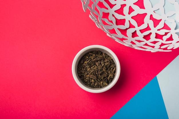 Folhas de chá secas na tigela branca contra o pano de fundo colorido