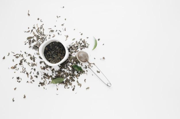 Folhas de chá seco com folhas de café e coador de chá no pano de fundo branco