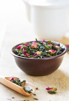 Folhas de chá verde com botões de rosa no bule de chá