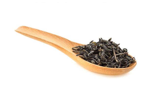 Folhas de chá verde secas em colher de madeira