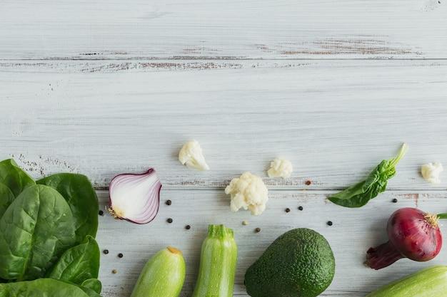 Folhas de couve-flor, abobrinha, cebola roxa, feijão verde, ovos, queijo e espinafre na mesa de madeira branca