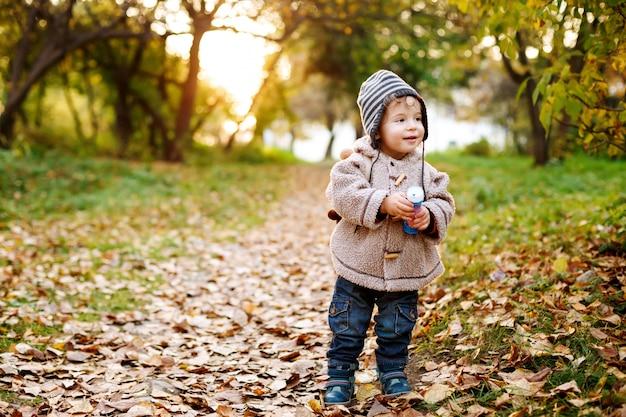 Folhas de criança pequena bonito pé no outono