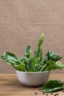 Folhas de espinafre em uma tigela de cerâmica. pimenta da jamaica e uma folha de espinafre na mesa. fundo de madeira. copie o espaço