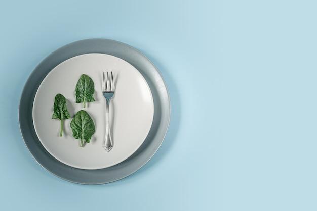 Folhas de espinafre verde e garfo em um prato na mesa azul, alimentação saudável e conceito de dieta