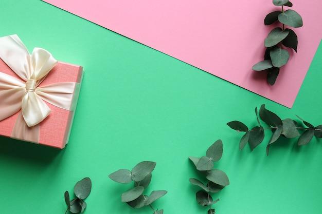 Folhas de eucalipto e caixa de presente sobre mesa rosa e azul-marinho