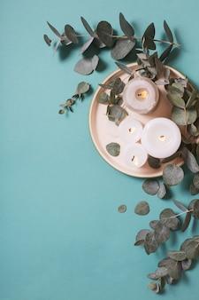 Folhas de eucalipto e velas acesas sobre fundo azul
