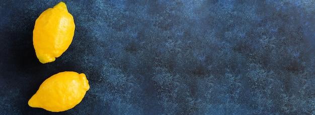 Folhas de hortelã, limão fresco e mel deitado segurando uma sacola de algodão de compras de malha em concreto azul.