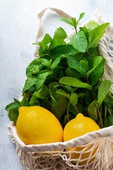 Folhas de hortelã, limão fresco e mel deitado segurando uma sacola de algodão de compras de malha em concreto cinza velho.